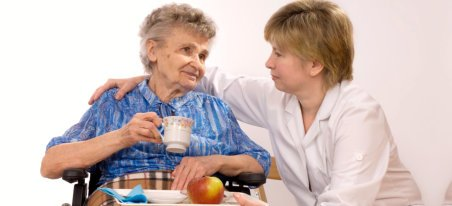 caregiver assisting patient in drinking water