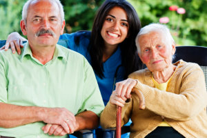 caregiver hugging two elderly patients