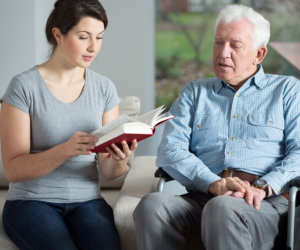 caregiver reading some book to elderly patient